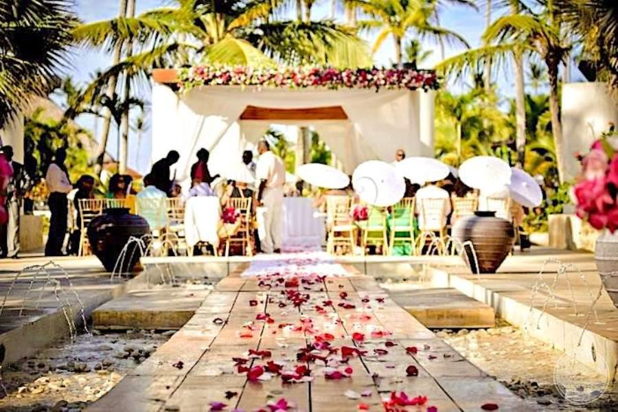 Garden wedding reception area with a gazebo and red flower petal surrounding the reception tables
