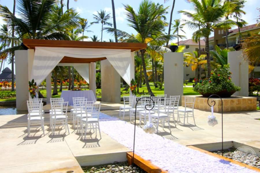 Wedding beach gazebo with white table chairs set up and white runner