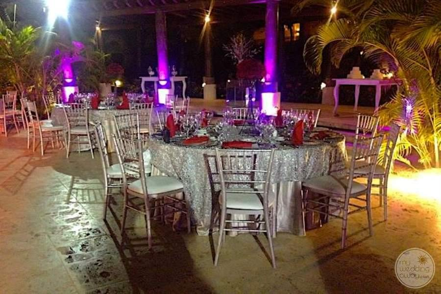 Outdoor wedding reception with silver table where is set up chairs on stone terrace