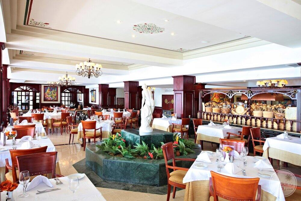 Main buffet restaurant at lunch with white linen tablecloths and would chairs