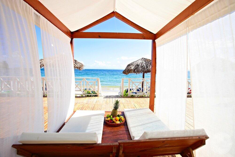 Two seater beach cabana with white linen drapes and a view of ocean