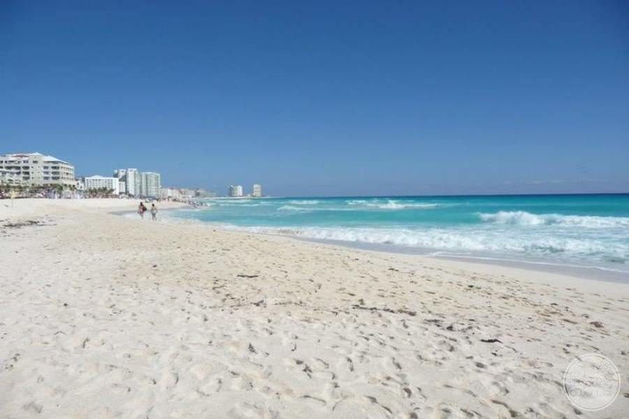 main white sand beach with long walk away to other hotels and aqua blue ocean