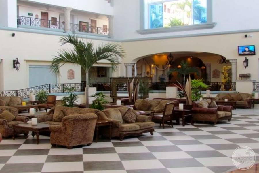 main lobby lounge area with overstaffed couches palm tree and reception