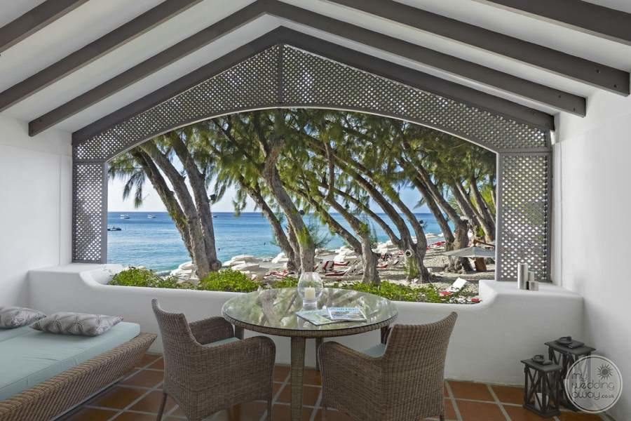 Balcony dining with a large sofa chair bed floor tiling and view of the beach and ocean
