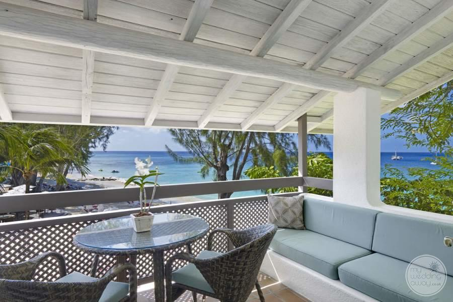 Outdoor seating area of the bedroom with table chairs and small couch area overlooking the ocean