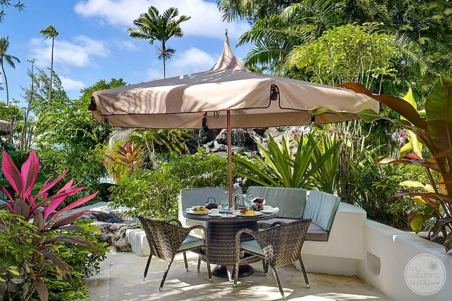 Outdoor restaurant area with light umbrella covering the table and beautiful tropical plants
