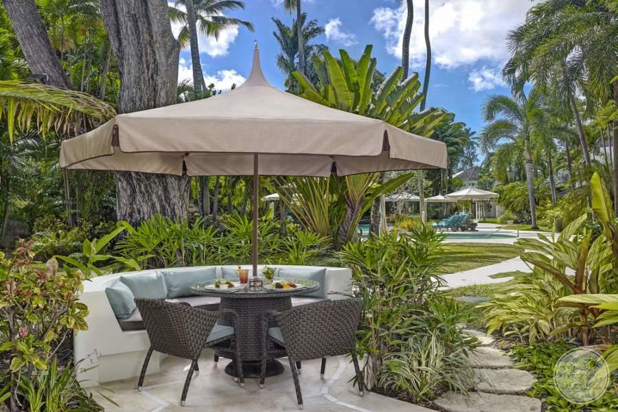 Open Terrace seating area for dining with brown umbrella and pathway to the beach