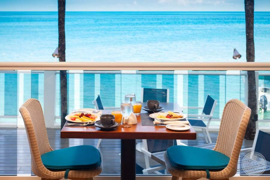 outdoor dining on brown rattan chairs with the lunch setting over looking the seaside