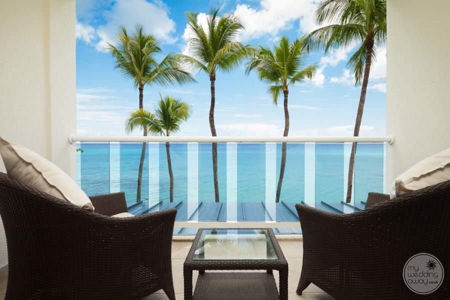 View of chair sitting on Outer deck of bedroom over looking the palm trees and ocean