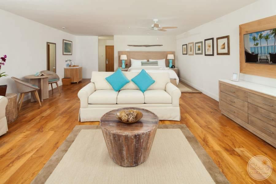 large bedroom with a beautiful hardwood floors wood table white couch and blue pillows
