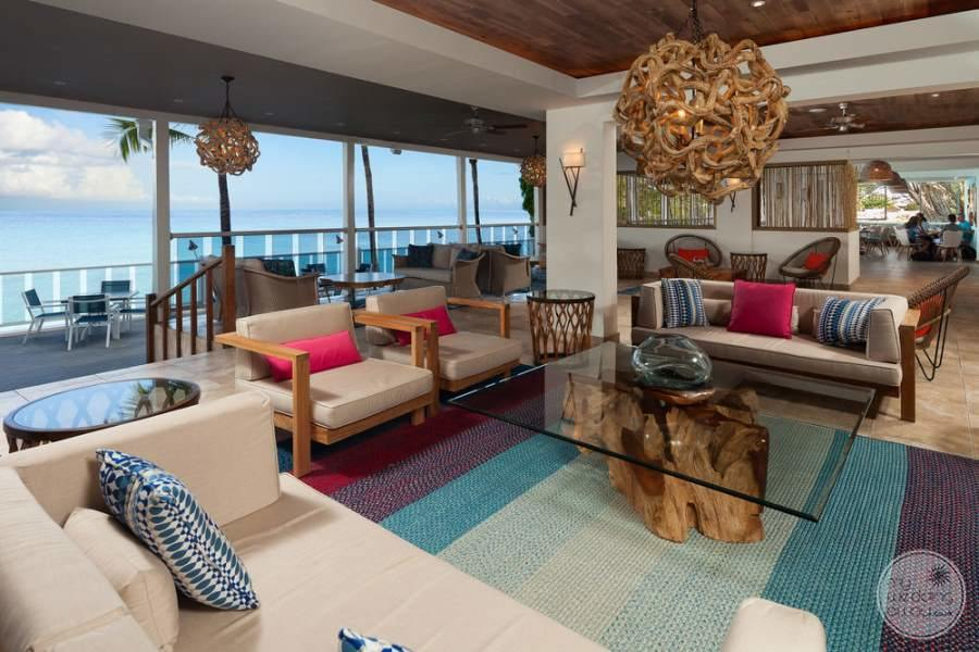 View of main lounge area with chairs and couches and tables set up for enjoying the ocean view