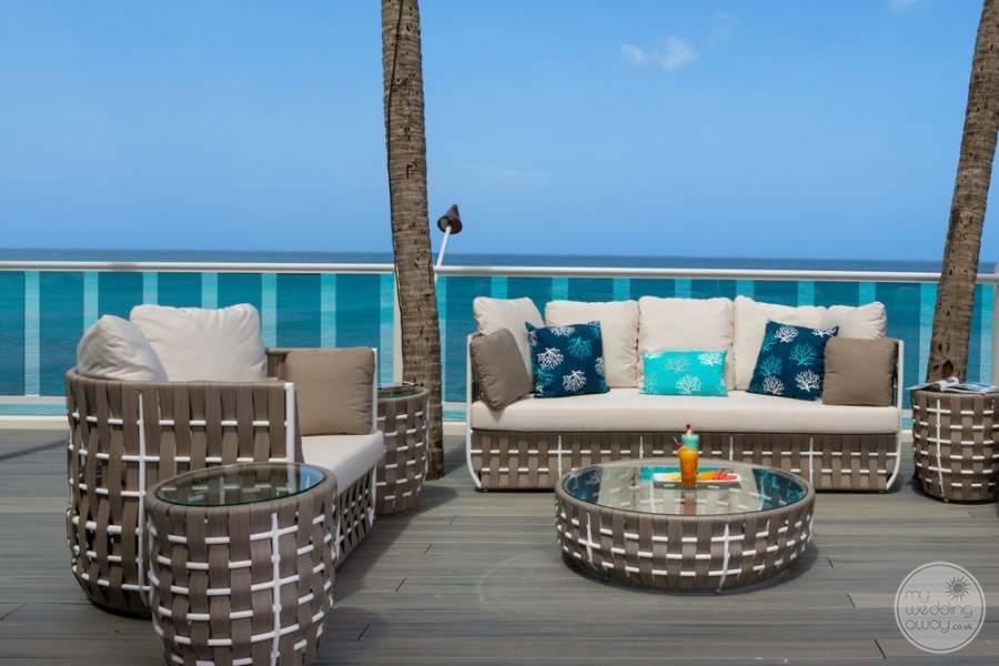 outdoor lounge seating with casual comfy white fluffy couches and blue pillows and tables