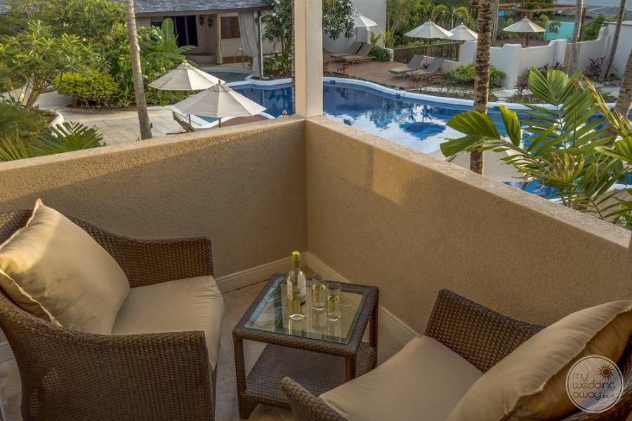 private balcony off of bedroom with fluffy brown lounge chairs in rattan overlooking the pool
