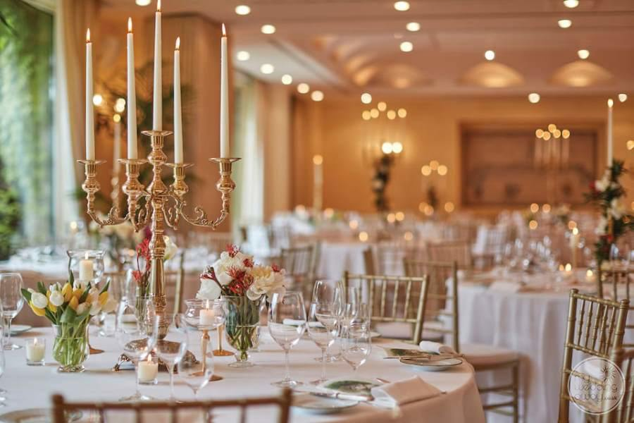 dining with a beautiful candelabra candles table seating with gold chairs and chandeliers