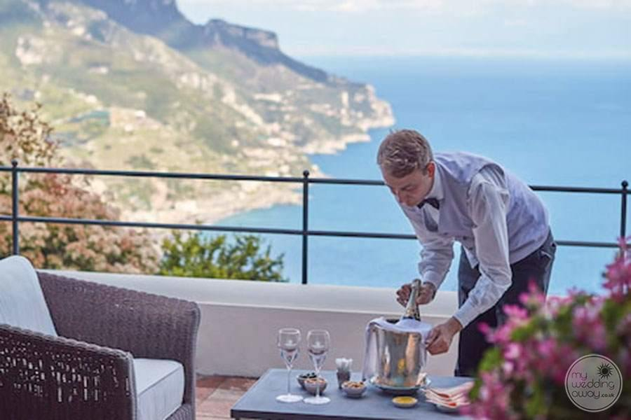 Terrace dining overlooking the ocean with maître d' serving champagne