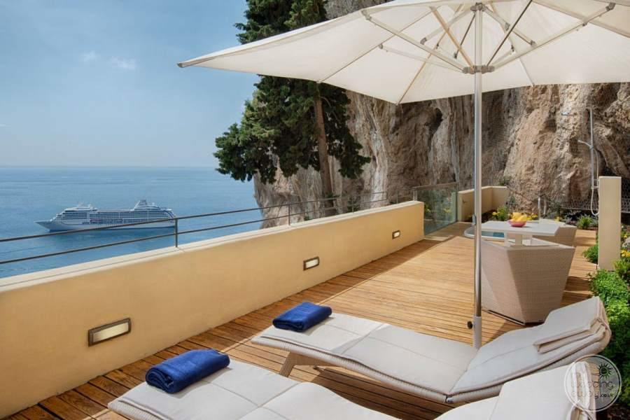 outer deck area on the cliff side with the wood decking white chairs and view of the ocean and ships passing bye