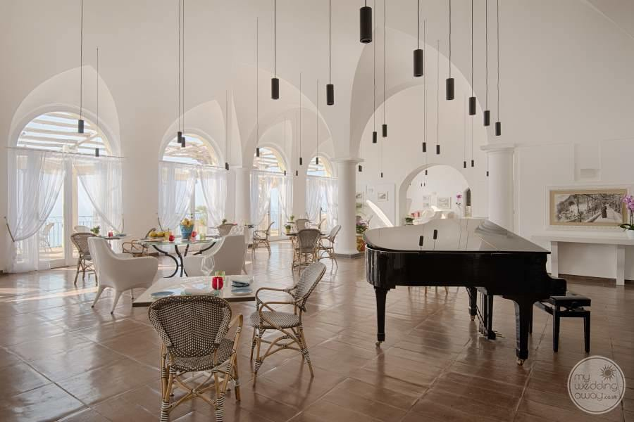 White high raise ceiling lounge area with grand piano white DeCora chairs and beautiful beige  tiling