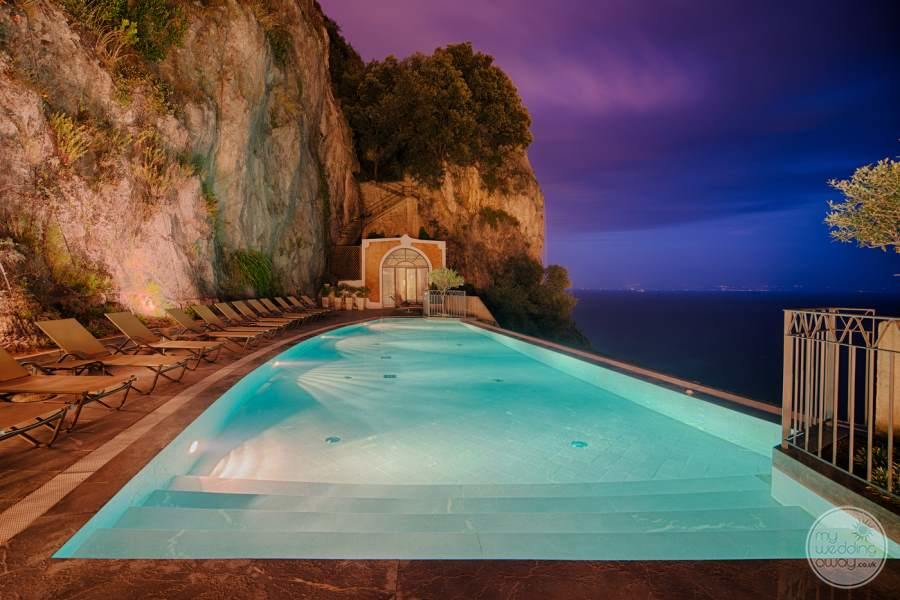 infinity pool in the evening beside a rock a cliff overlooking the ocean
