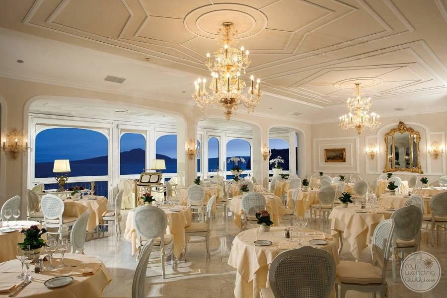 main dining room with a beautiful white DeCora chairs chandeliers and breathtaking view of the ocean at night