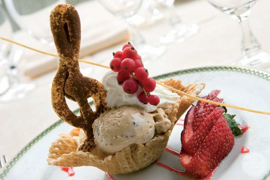 gourmet dessert ice cream and waffle cone dish and fresh strawberries
