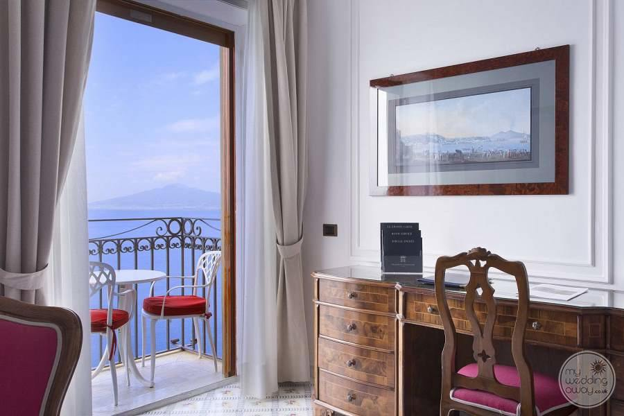 bedroom with beautiful desk pink chair and outer balcony overlooking the ocean