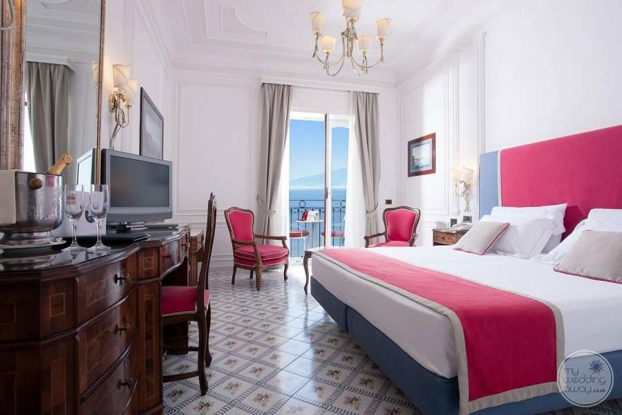 room with beautiful pink bedspread cover white tiling and view of ocean