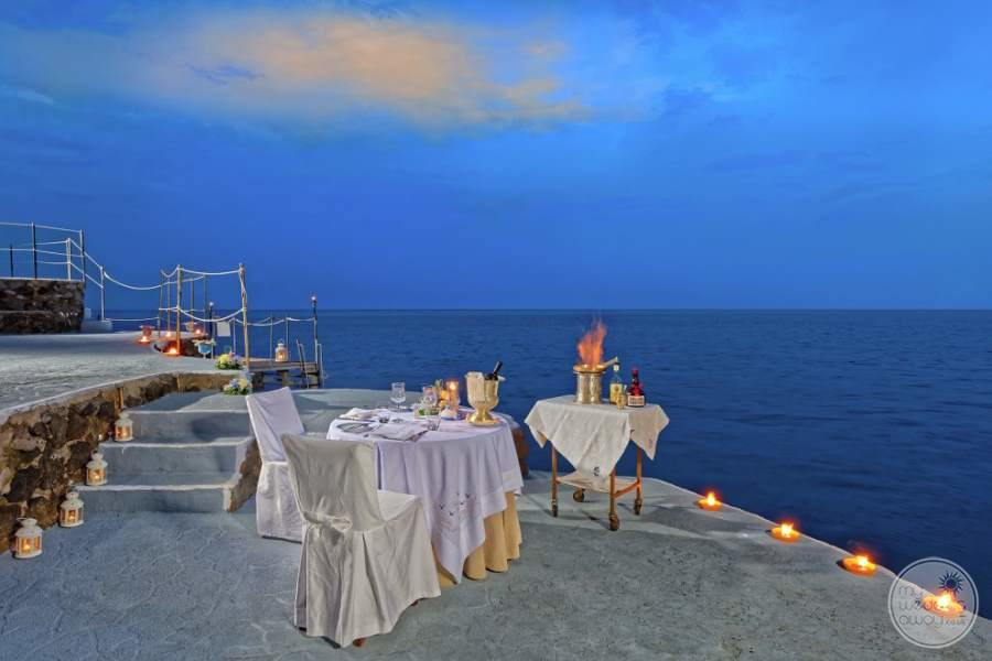 Dining for two out on the terrace overlooking the ocean at night