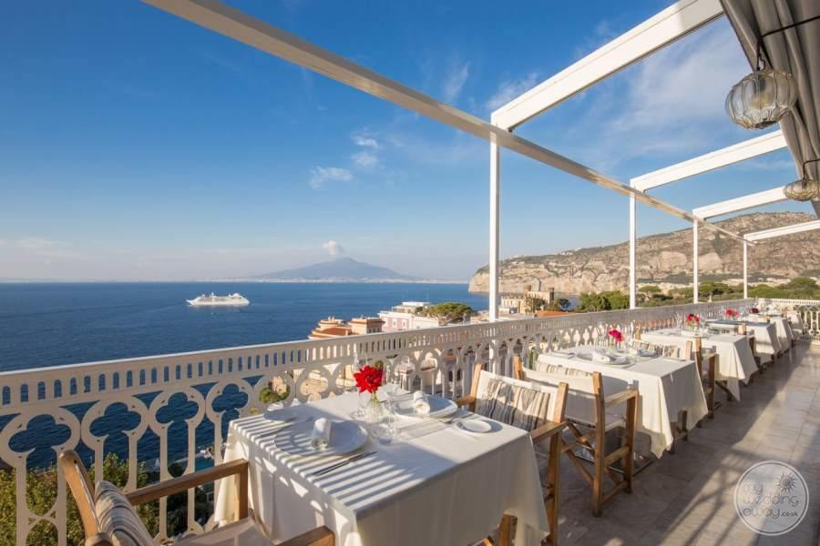 Outdoor dining on terrace overlooking the ocean with a ship in the background