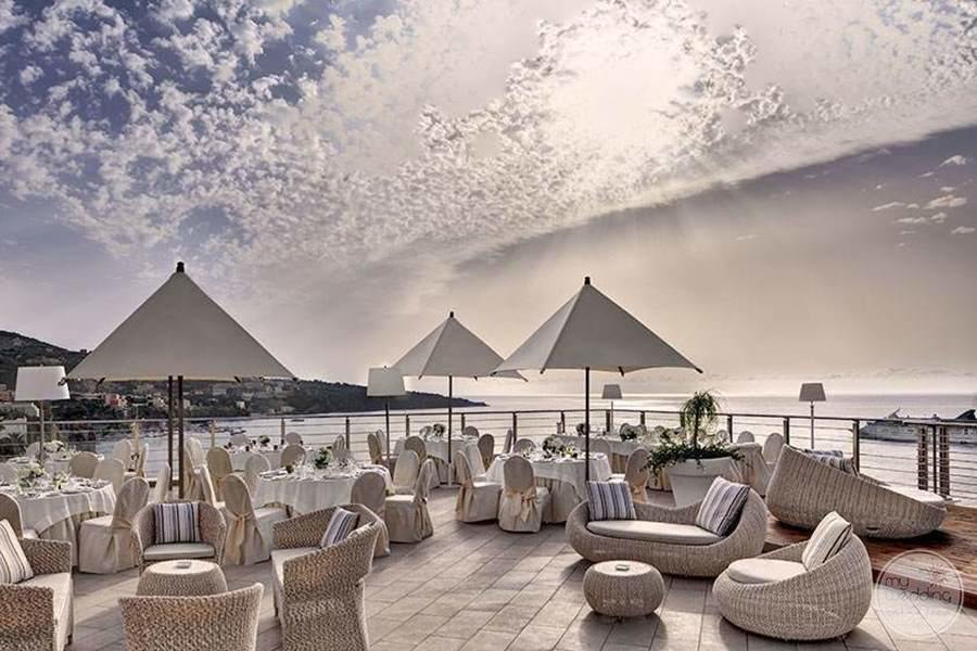 Outdoor venue of Terrace seating with the views of the ocean at sunset