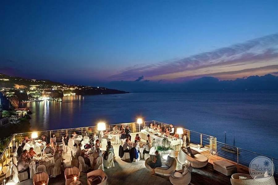 Evening wedding reception with gas sitting out on the terrace overlooking the ocean
