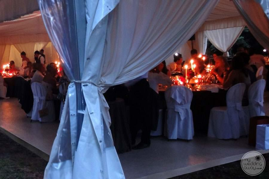 Evening wedding reception with guests sitting at tables with candle lights
