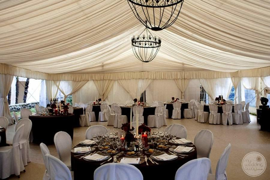 Indoor wedding reception area with white covered chairsAnd beautiful table Decour