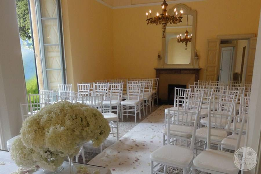 Indoor wedding ceremony venue with white chairs and flowers