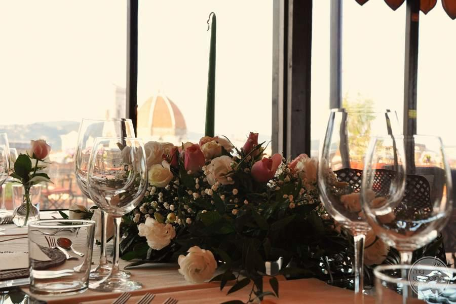 Dining area with flower bouquet on table and city view