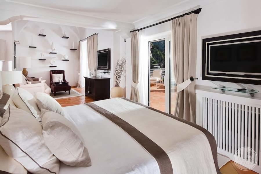 king bed Room with white artwork on the walls and flat screen TV