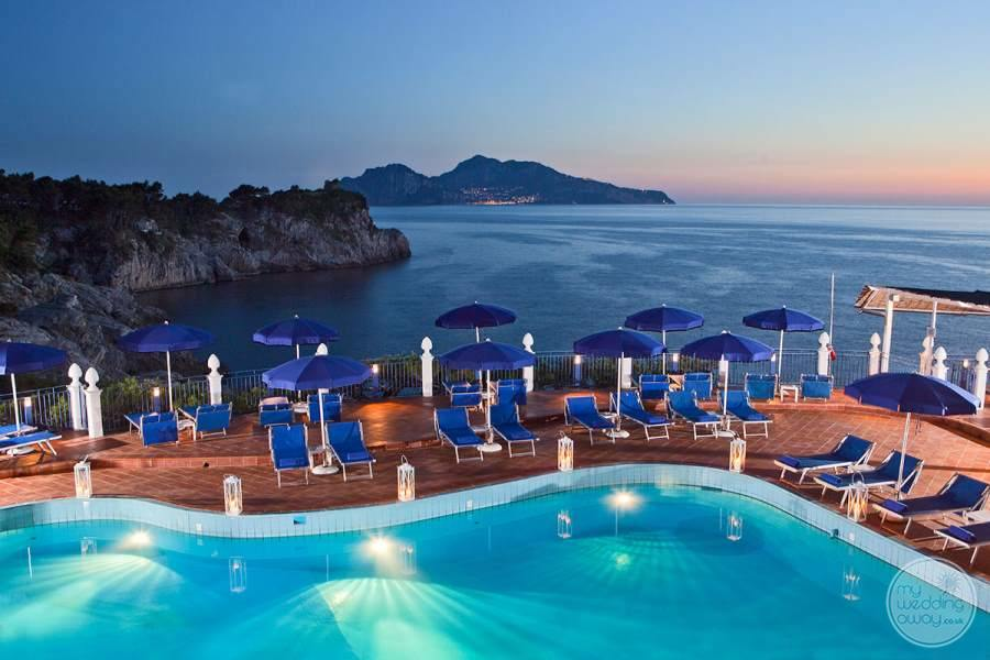 main Pool with lounge chairs in the evening