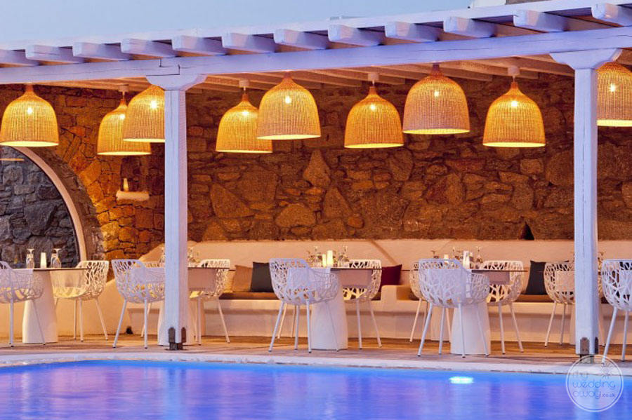 Poolside Dining with wood ceiling lighting and white decorative chairs by pool