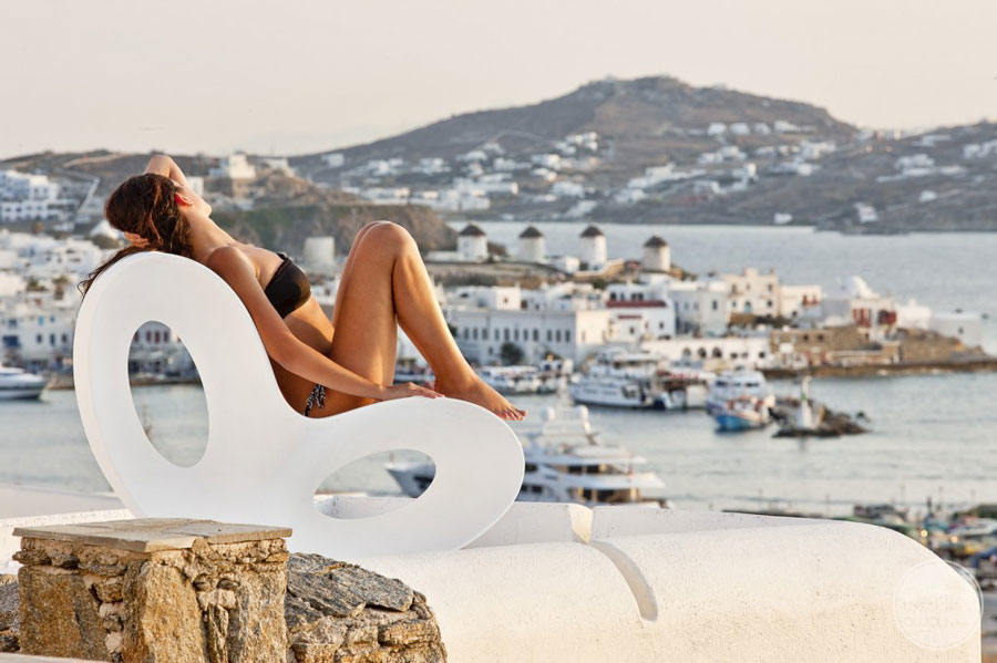 Sunbather woman on deck chair overlooking town