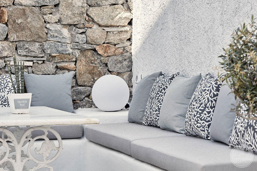Lounge Area with white and black cushions and rock feature wall