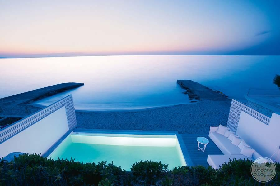 View of ocean and room infinity pool and lounge couch at sunset
