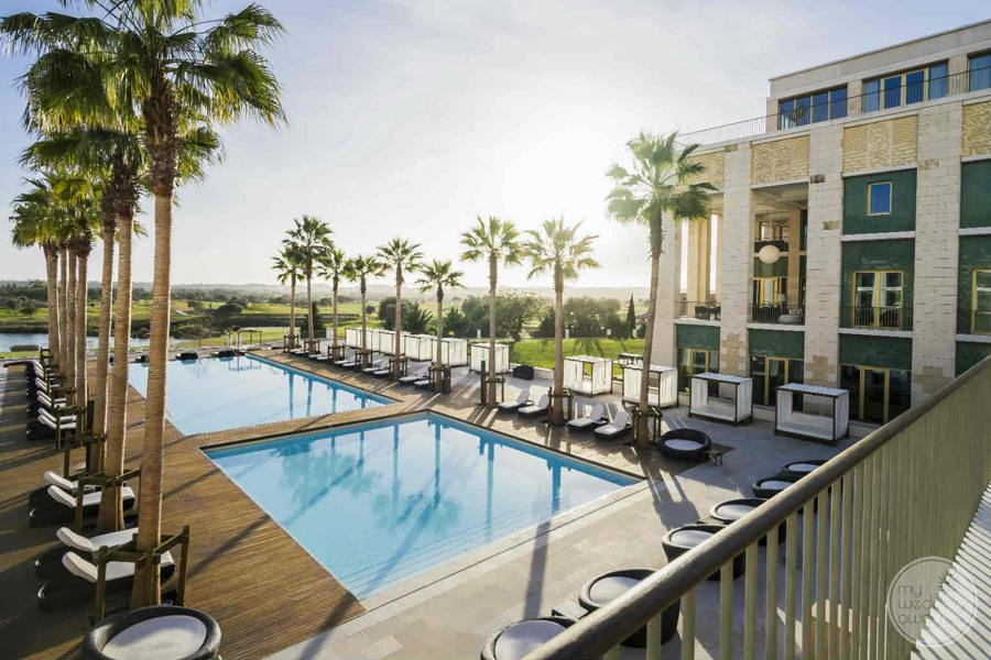 Anantara Vilamoura pool and lounging area with palm trees