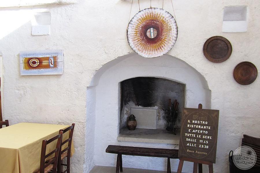 Masseria L'Antico Frantoio Hotel restaurant fireplace around tables