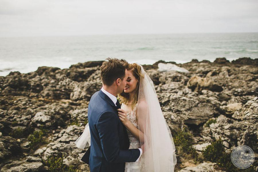wedding couple at beach by the ocean kissing