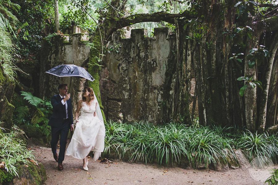 garden area with bride and groom holding umbrella