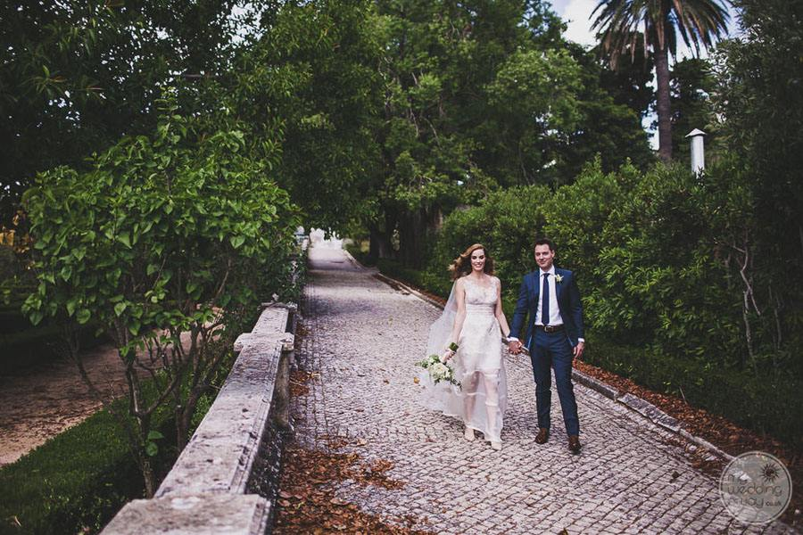 bride and groom on garden path with bouquet