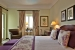 Palacio-Estoril-Hotel-mauve-bedroom with lounge-chair