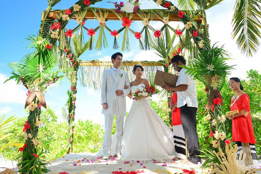Resort Wedding couple exchanging vows with floral decorated gazebo