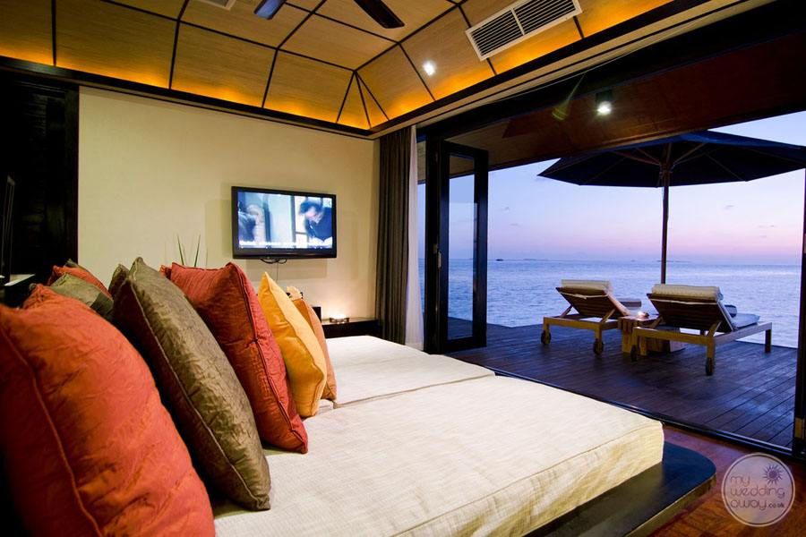 Kind Bedroom with multi coloured pillows and oceanfront view