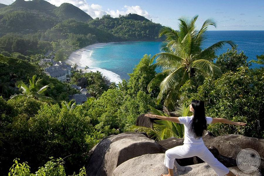 Yoga instructor on resort clifftop overlooking ocean