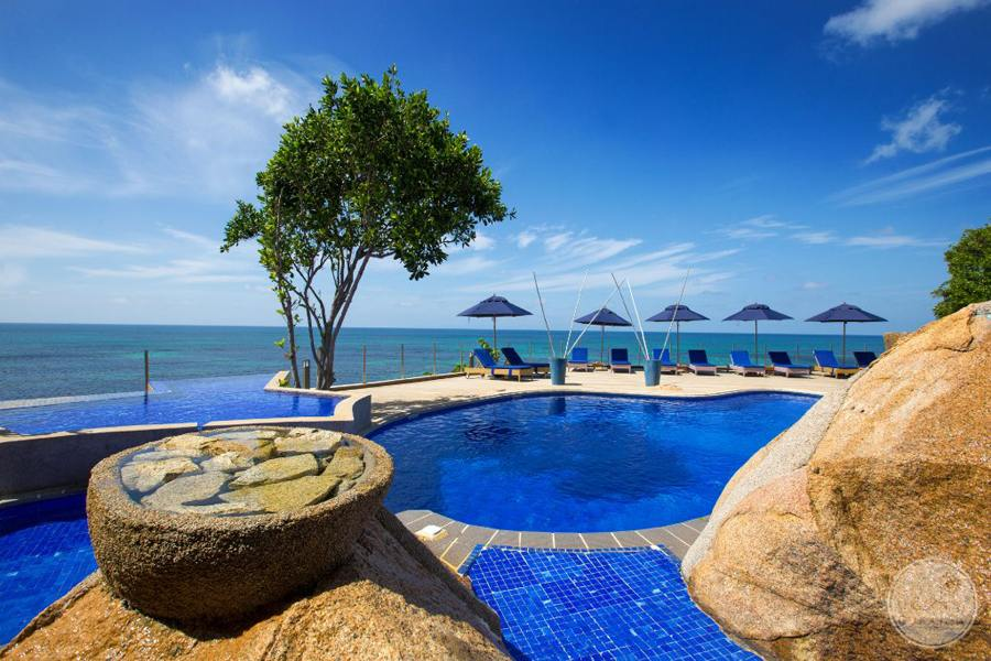 Hotel infinity Pool surrounded by decorative rocks and ocean